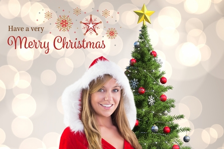 Beautiful woman in santa costume standing near christmas tree against digitally generated background