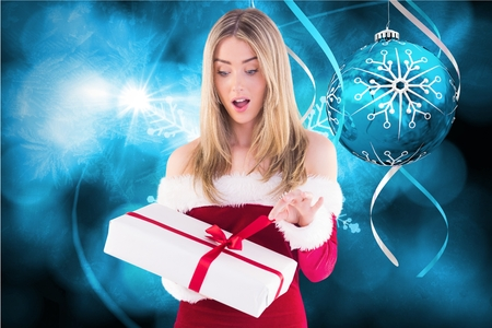 Excited woman in santa costume opening christmas gift against digitally generated background