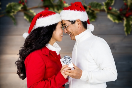 Couple in santa hat holding a gift during christmas time