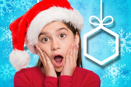 Surprised girl in santa hat against digitally generated background during christmas time