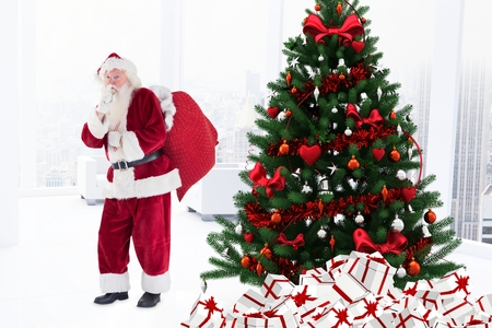 Portrait of santa claus with finger on lips standing near christmas tree during christmas time Stock Photo