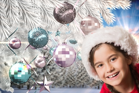 christmas time: Portrait of happy girl in santa hat against digitally generated background during christmas time