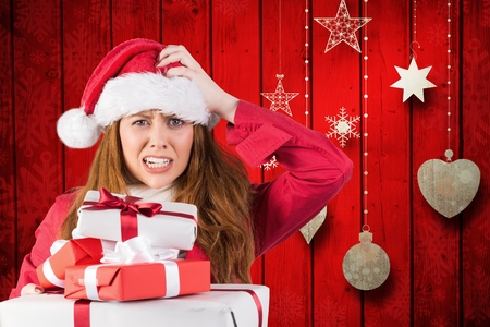 Portrait of confused woman in santa costume with a stack of christmas gifts Stock Photo