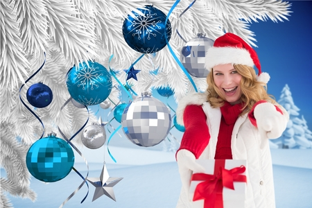tinsel: Portrait of excited woman in santa hat showing her gift against digitally generated christmas background Stock Photo