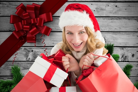 christmas time: Portrait of excited woman in santa hat holding gifts during christmas time