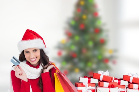 woman holding card: Beautiful woman in santa hat holding credit card and shopping bags during christmas time Stock Photo