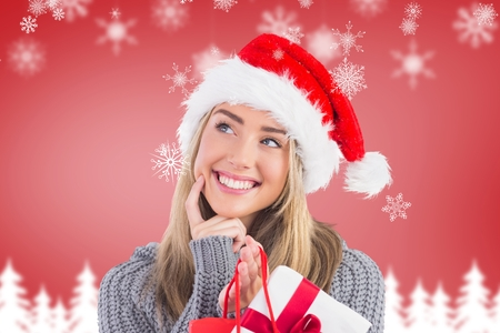 christmas time: Portrait of smiling woman in santa hat holding a gift bag during christmas time