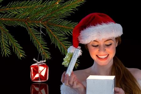 pere noel sexy: Heureuse femme dans le chapeau de santa ouvrant sa boîte cadeau dans la nuit pendant le temps de Noël