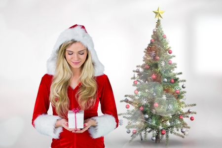 hooded vest: Beautiful woman in Santa costume holding gift  during christmas time