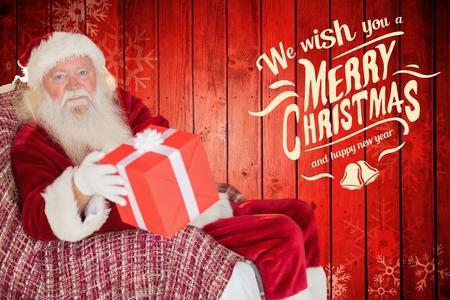 pere noel sexy: Portrait de père noël tenant cadeau de Noël sur fond généré numériquement