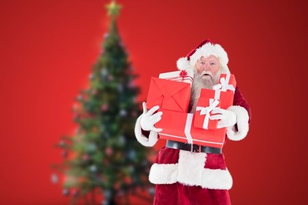 Portrait of santa claus holding stack of christmas gifts