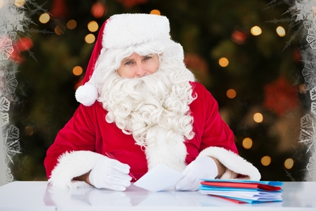 christmas list: Portrait of santa claus sitting while making a check list during christmas time Stock Photo