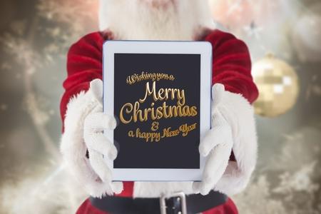 サンタ クロースがクリスマスの時間の間にデジタル タブレット画面にクリスマスと新年の挨拶を表示