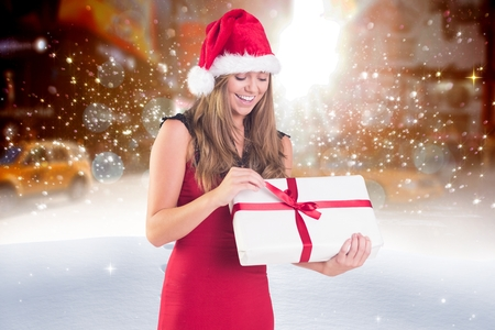 Happy woman in santa hat opening her christmas gift against digitally generated sparkling background