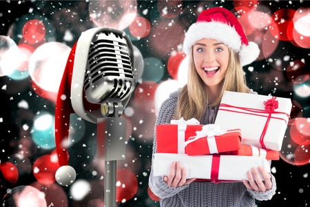 Excited woman in santa hat holding stack of gifts against digitally generated christmas background