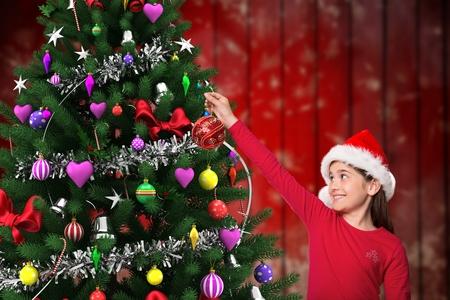 pelo castaño claro: Chica en el sombrero de santa que adorna el árbol de navidad con la chuchería Foto de archivo