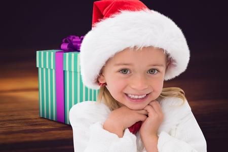 Excited girl in santa hat smiling at camera during christmas time