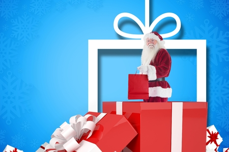 christmas time: Portrait of santa claus holding shopping bag while standing inside gift box during christmas time Stock Photo