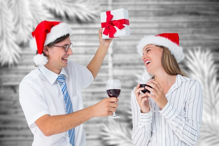 gesturing: Happy couple in santa hat holding gift and glass of wine during christmas time