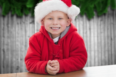pere noel sexy: Portrait of boy in santa hat smiling at camera during christmas time