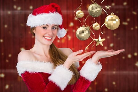 Portrait of beautiful woman in santa costume pretending to hold imaginary christmas decoration