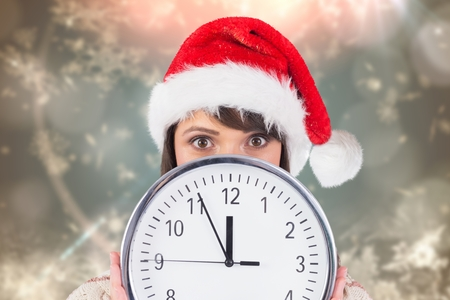Portrait of anxious woman in santa hat holding a clock