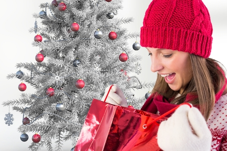 Close-up of excited woman in red beanie cap checking her christmas gifts Stock Photo
