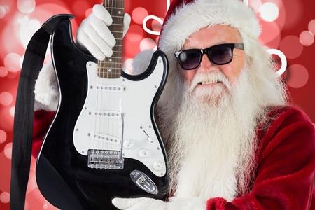 pere noel sexy: Père Noël dans des lunettes de soleil tenant la guitare pendant le temps de Noël