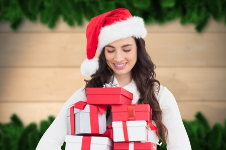 pelo castaño claro: Beautiful woman in santa hat looking at gifts during christmas time