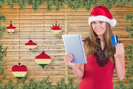 christmas time: Beautiful woman in santa hat doing online shopping with credit card on digital tablet during christmas time