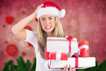christmas time: Portrait of frustrated woman in santa hat holding stack of gifts during christmas time Stock Photo