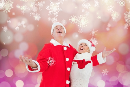 christmas time: Happy couple in santa costume pretending to catch  snowflakes during christmas time Stock Photo