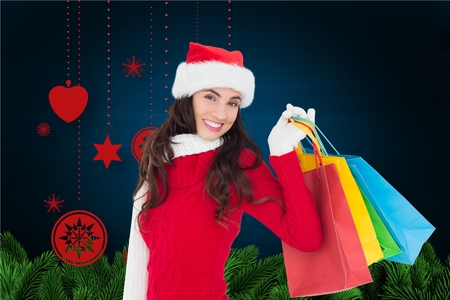 pere noel sexy: Portrait of smiling woman holding her shopping bags against digitally generated christmas background