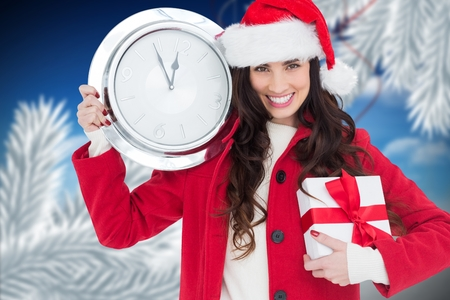 Smiling woman in santa hat holding gift and a wall clock showing few minutes to midnight during christmas time Stock Photo