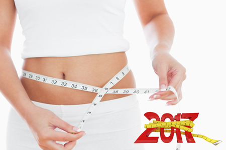 midsection: Midsection of woman measuring waist against digitally generated image of new year with tape measure Stock Photo