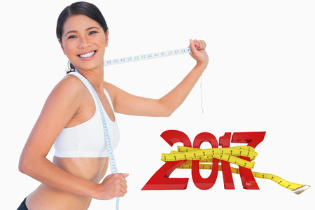 Smiling slim woman playing with her measuring tape against digitally generated image of new year with tape measure