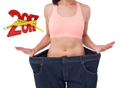 waist weight: Woman showing her waist after losing weight against digitally generated image of new year with tape measure Stock Photo