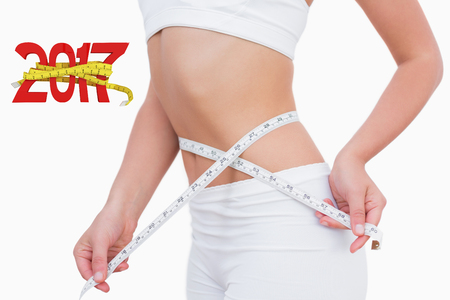 digitally generated image: Midsection of woman measuring waist against digitally generated image of new year with tape measure Stock Photo