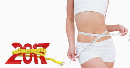 midsection: Midsection of slim woman measuring waist against new year with tape measure