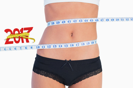 digitally generated image: Slim belly surrounded by measuring tape against digitally generated image of new year with tape measure Stock Photo