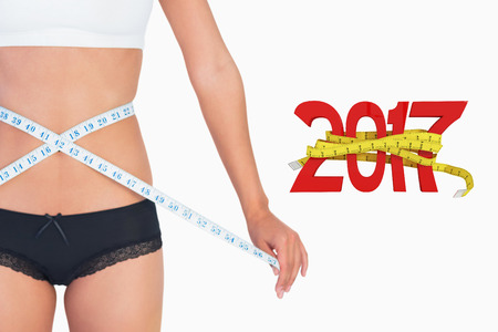 waist: Cheerful slim woman measuring her waist against digitally generated image of new year with tape measure Stock Photo