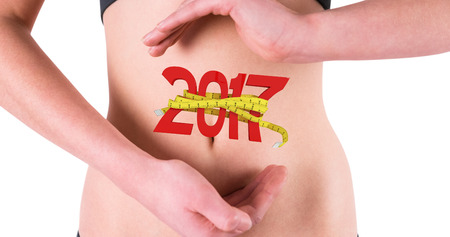 digitally generated image: Woman with hands over belly against digitally generated image of new year with tape measure Stock Photo