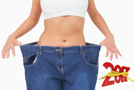 midsection: Digitally generated image of new year with tape measure against midsection of young slim woman wearing jeans Stock Photo