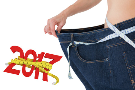 waist weight: Woman waist who lost a lot of weight against digitally generated image of new year with tape measure Stock Photo