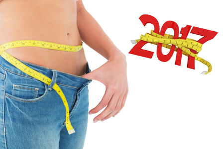sized: Mid section of woman measuring waist in a big sized jeans against digitally generated image of new year with tape measure Stock Photo