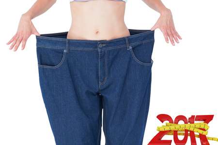 digitally generated image: Woman wearing too large pants  against digitally generated image of new year with tape measure Stock Photo
