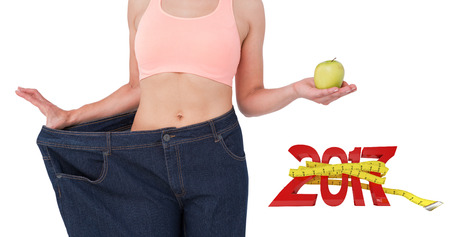 waist weight: Woman showing her waist after losing weight against new year with tape measure