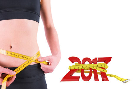 waist: Slim woman measuring waist with tape measure against digitally generated image of new year with tape measure