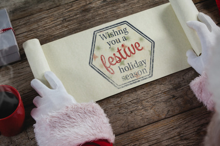 santa suit: Close-up of santa claus opening scroll against print wishng you a festive holiday season Stock Photo