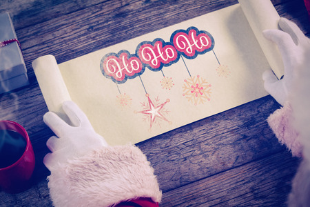 santa suit: Close-up of santa claus opening scroll against white and red greetings card
